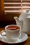 Tasse de thé avec la théière dans la perspective des abat-jour Photo stock