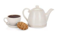 Tasse de thé avec la théière et un biscuit sur le blanc Photo libre de droits