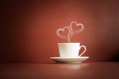 Tasse de thé avec la vapeur dans la forme de deux coeurs Photos libres de droits