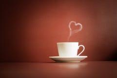 Tasse de thé avec la vapeur dans une forme de coeur Photo libre de droits