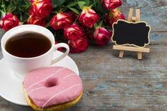 Tasse de thé avec le beignet, les roses fraîches et le tableau noir avec l'espace pour Images stock