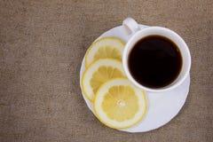 Tasse de thé avec le citron sur la toile de jute Images stock