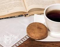 Tasse de thé avec le gâteau, le livre et le napperon Photographie stock