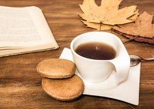 Tasse de thé avec le gâteau, le livre et les feuilles Image libre de droits
