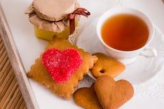 Tasse de thé avec les biscuits en forme de coeur Biscuits de rouge de sucre Photographie stock libre de droits