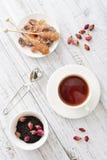 Tasse de thé avec les bourgeons roses secs Photographie stock libre de droits