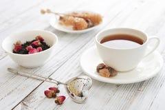 Tasse de thé avec les bourgeons roses secs Images libres de droits