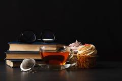 Tasse de thé avec les bourgeons roses secs et les vieux livres dans la nuit Photographie stock