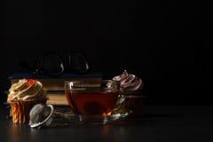 Tasse de thé avec les bourgeons roses secs et les vieux livres dans la nuit Photographie stock libre de droits