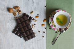 Tasse de thé avec sur la vieille barre de chocolat de toile en bon état de table f Photo stock