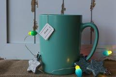 Tasse de thé avec une étiquette rêveuse, des ornements d'étoile, et des lumières Photos libres de droits