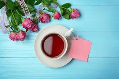 Tasse de thé, de carte vide et de roses Photo stock