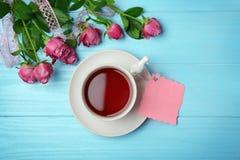 Tasse de thé, de carte vide et de roses Photo stock