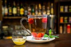 Tasse de thé chaud de framboise d'hiver avec des bâtons de cannelle Photographie stock