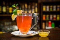 Tasse de thé chaud de framboise d'hiver avec des bâtons de cannelle Images stock
