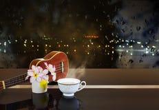 Tasse de thé chaud ou de boisson chaude avec les fleurs et l'ukulélé en Li de nuit Image stock
