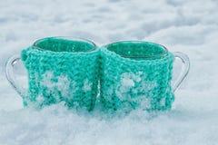 Tasse de thé colorée par menthe dans la neige Photo stock