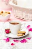 Tasse de thé décorée des pétales de rose Photo stock
