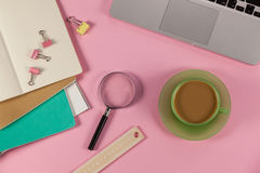 Tasse de thé, d'ordinateur portable, de loupe, de journaux intimes, de règle et de trombones Photographie stock