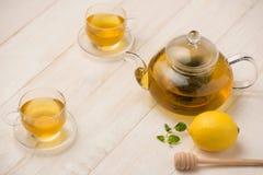 Tasse de thé de citron avec du miel sur le fond en bois blanc Photo stock