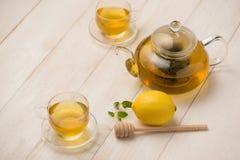 Tasse de thé de citron avec du miel sur le fond en bois blanc Photos libres de droits