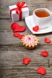 Tasse de thé, de gâteau et de coeurs rouges Photographie stock