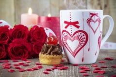 Tasse de thé devant le bouquet des roses rouges Photographie stock libre de droits