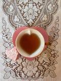 Tasse de thé en forme de coeur rose avec le gâteau givré en forme de coeur Photographie stock libre de droits