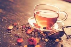 Tasse de thé en verre avec les boutons de rose secs Photographie stock