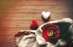 Tasse de thé et écharpe avec des formes de coeur Images stock