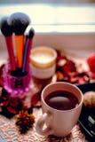 Tasse de thé et accessoires femelles sur la table Les cosmétiques de bonbons mirent des pétales de rose Concept femelle image stock