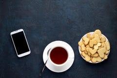 Tasse de thé et biscuits et smartphone en forme de coeur sur le fond en pierre Photo stock