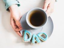 Tasse de thé et de biscuits parfumés sous forme de lettres D A D Image stock