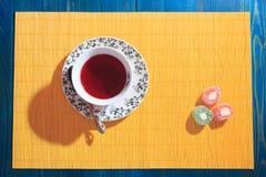 Tasse de thé et bonbons sur le fond jaune Image libre de droits