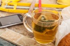 Tasse de thé et smartphone dans l'intérieur malpropre Photos stock