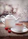 Tasse de thé et théière avec les coeurs rouges   dans le jour givré d'hiver Photo stock