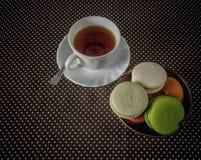 Tasse de thé et un panier des macarons sur la table Photos libres de droits