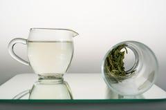 Tasse de thé et verre avec des feuilles de thé avec la réflexion Images libres de droits