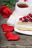 Tasse de thé, morceau de gâteau et coeur rouge Photos stock