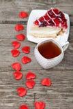Tasse de thé, morceau de gâteau et coeur rouge Photographie stock