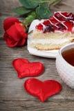 Tasse de thé, morceau de gâteau et coeur rouge Image stock