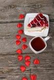 Tasse de thé, morceau de gâteau et coeur rouge Photo stock