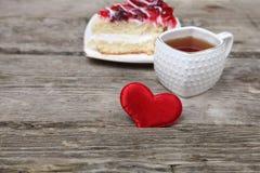 Tasse de thé, morceau de gâteau et coeur rouge Images libres de droits