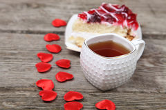 Tasse de thé, morceau de gâteau et coeur rouge Images stock
