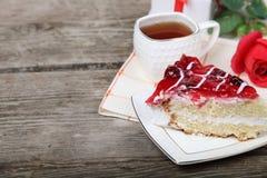 Tasse de thé, morceau de gâteau et rose de rouge Image stock