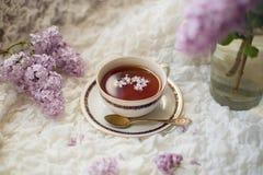 Tasse de thé noir aromatique avec la branche lilas Photographie stock