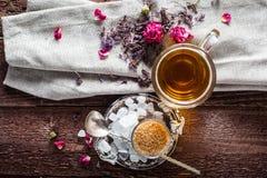 Tasse de thé noir avec la canne à sucre, roses, feuilles de thé sur un fond en bois brun Photographie stock libre de droits