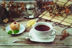 Tasse de thé noir avec le petit pain Image libre de droits