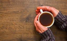 Tasse de thé noir dans les mains de l'homme Sur un fond en bois Avec l'espace de copie Photographie stock