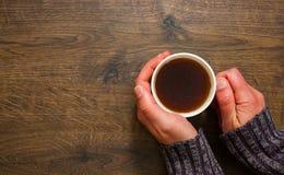 Tasse de thé noir dans les mains de l'homme Sur un fond en bois Avec l'espace de copie Image stock
